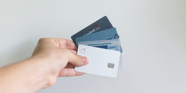 A photo of a hand holding four credit cards.